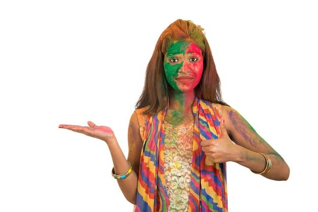 Молодая женщина с красочным лицом держит и представляет что-то в руке со счастливой улыбкой по случаю фестиваля холи. концепция фестиваля и технологии.