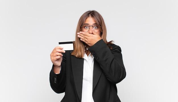 Молодая женщина с кредитной картой прикрывает рот руками с шокированным, удивленным выражением лица, хранит секрет или говорит: ой