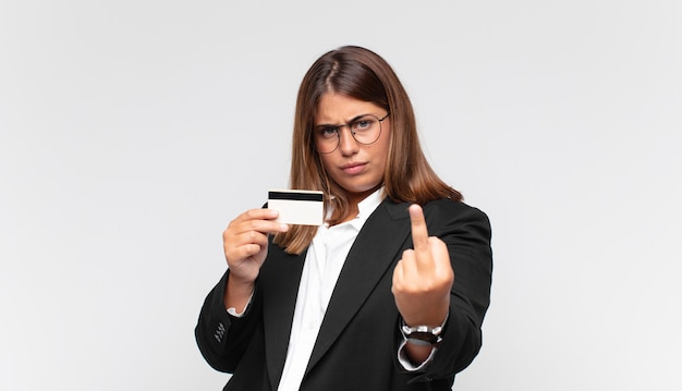 Молодая женщина с кредитной картой чувствует себя сердитой, раздраженной, мятежной и агрессивной, щелкает средним пальцем, сопротивляется