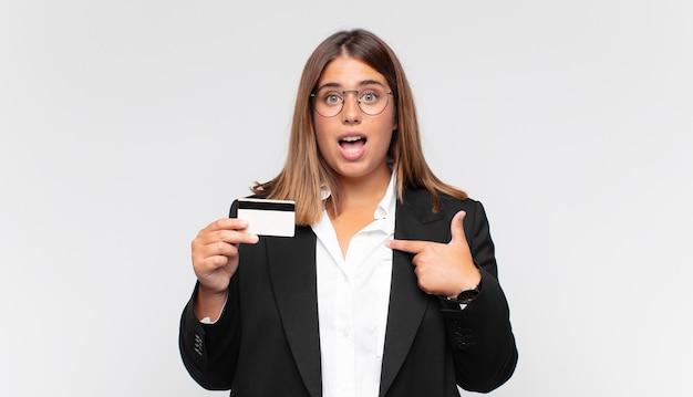 Молодая женщина с кредитной картой чувствует себя счастливой, удивленной и гордой, указывая на себя взволнованным, изумленным взглядом