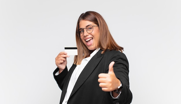 신용 카드를 가진 젊은 여성이 자랑스럽고 평온하며 자신감 있고 행복하다고 느끼고 엄지손가락을 치켜들고 긍정적으로 웃고 있습니다.