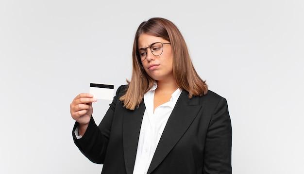 신용 카드를 가진 젊은 여성이 슬프고 화 나거나 화가 나고 부정적인 태도로 측면을 바라보고 의견이 일치하지 않습니다.