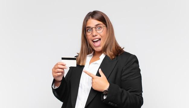신용 카드를 들고 있는 젊은 여성이 흥분하고 놀란 듯 옆과 위쪽을 가리키며 공간을 복사합니다.