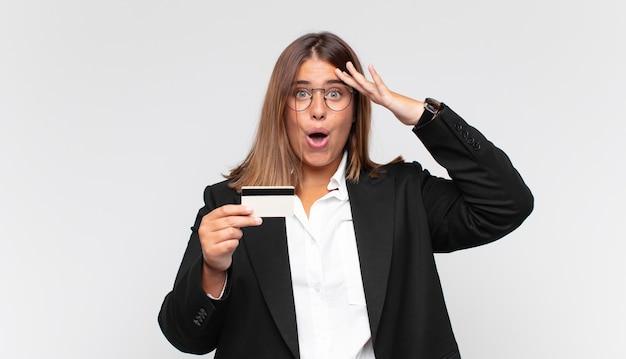 신용 카드를 가진 젊은 여성이 행복하고 놀라고 놀라고 웃고 놀랍고 놀라운 좋은 소식을 깨닫고 있습니다.