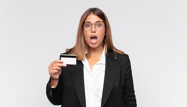 신용 카드를 가진 젊은 여성이 매우 충격을 받거나 놀란 것처럼 보이며 입을 벌리고 와우