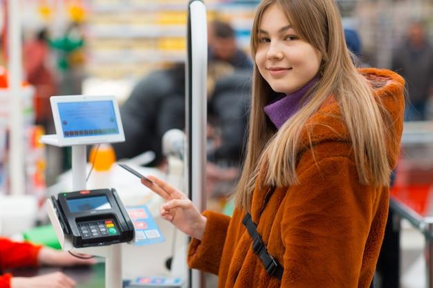 Молодая женщина с помощью кредитной карты оплачивает покупки на кассе в магазине