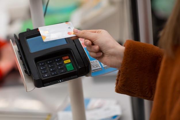 신용 카드를 가진 젊은 여자는 상점의 계산대에서 구매 비용을 지불합니다.