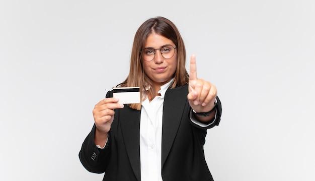 신용 카드가 자랑스럽게 웃고 자신있게 넘버원 포즈를 승리로 만드는 젊은 여성, 리더가 된 느낌