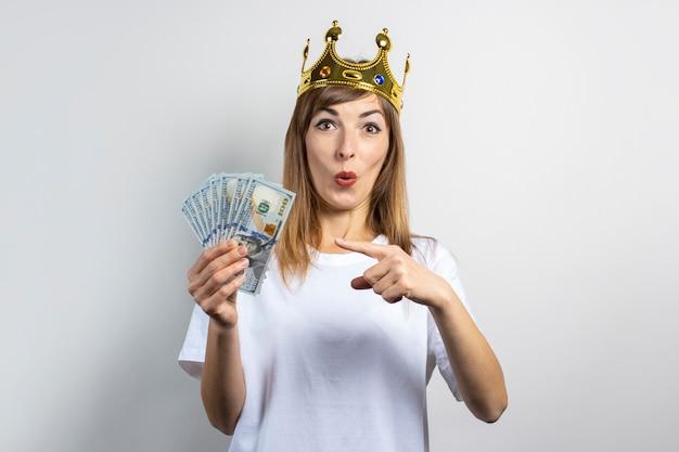 彼女の頭には王冠と驚いた顔を持つ若い女性は明るい背景にお金のスタックを保持しています。