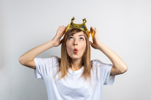 Молодая женщина с короной на голове и удивленным лицом.