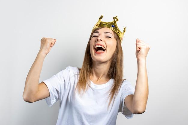 Молодая женщина с короной на голове эмоционально радуется и празднует
