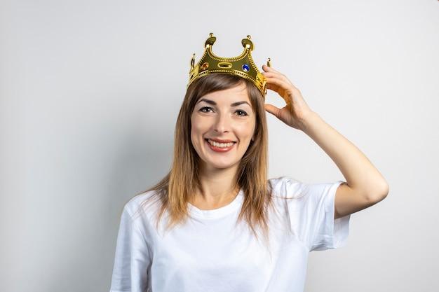 Молодая женщина с короной на голове на светлом фоне
