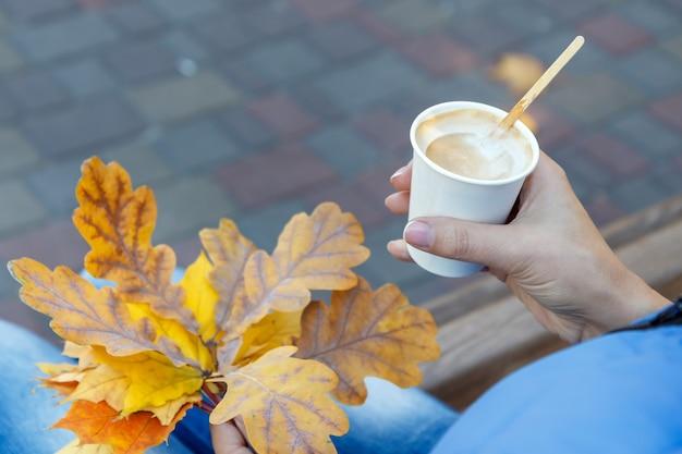 一杯のコーヒーと紅葉を持つ若い女性。