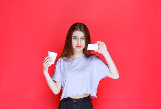 彼女の名刺を提示する飲み物のカップを持つ若い女性。