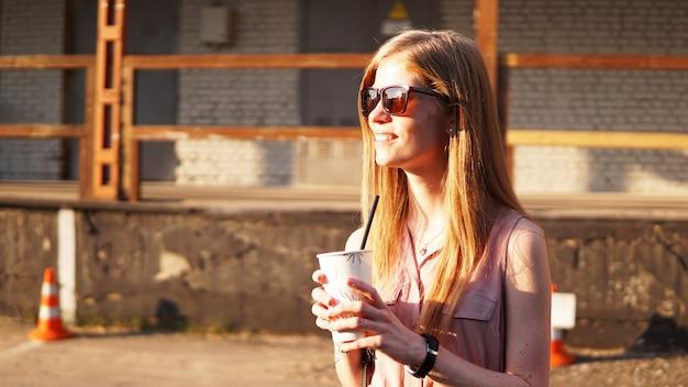 Молодая женщина с чашкой лимонада за пределами солнечного дня и городского фуд-корта