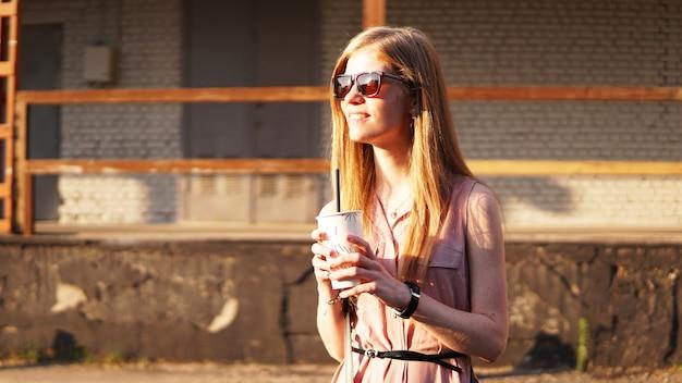 晴れた日と都会のフードコートの外でレモネードのカップを持つ若い女性