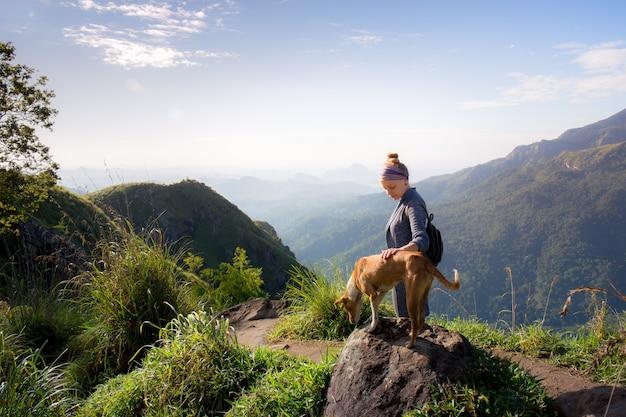 산 꼭대기에 강아지와 함께 젊은 여자