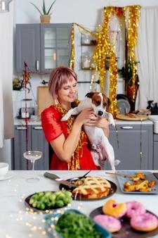 パーティーの後、キッチンに座っている犬を持つ若い女性