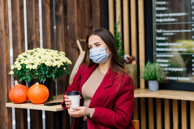 레스토랑에서 얼굴 마스크를 가진 젊은 여성, 코로나 바이러스 전염병을 보호하기위한 새로운 일반 개념