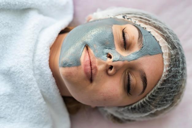 얼굴 마스크를 쓴 젊은 여성이 미용실의 침대에 누워 있습니다. 건강 관리의 개념