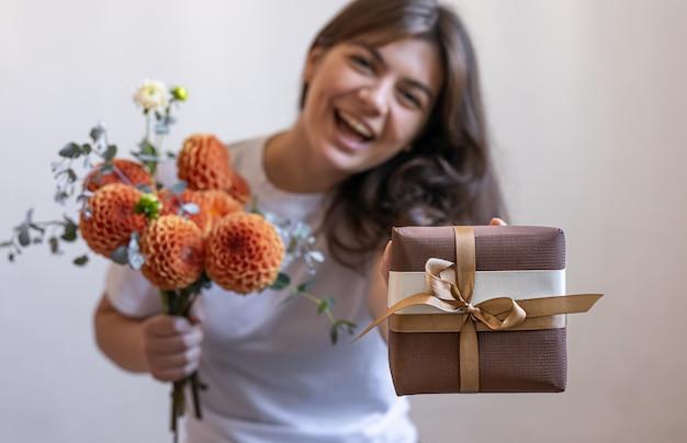 Молодая женщина с подарочной коробкой и букетом цветов хризантемы