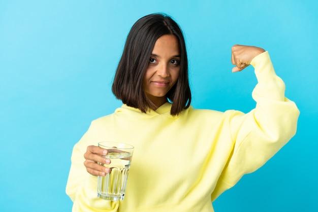 강한 제스처를 하 고 파란색 벽에 절연 물 한 잔을 가진 젊은 여자