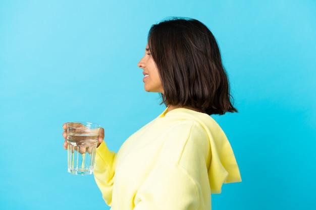 노력을 한 데 대한 요통으로 고통 파란색 벽에 절연 물 한 잔을 가진 젊은 여자