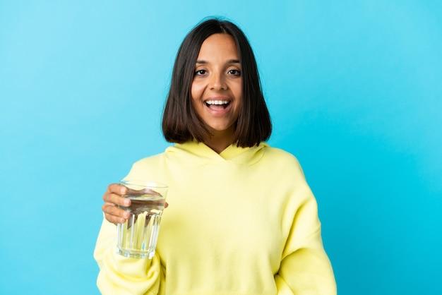놀라운 표정으로 파란색 벽에 절연 물 한 잔을 가진 젊은 여자
