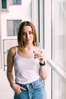 방에있는 소파에 앉아 물 한 잔을 가진 젊은 여자 프리미엄 사진