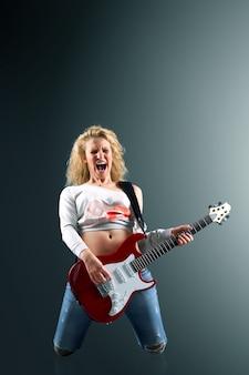 기타를 가진 젊은 여자는 록 노래를 노래