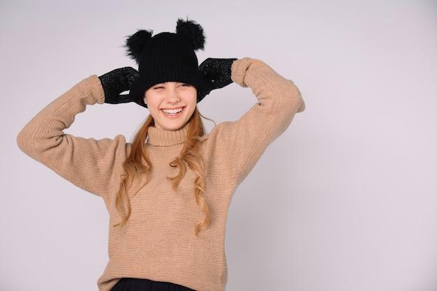 Молодая женщина со счастливым смехом в зимней шапке и перчатках