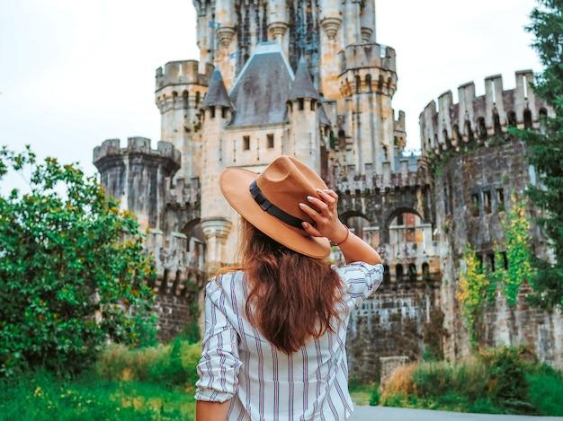 Молодая женщина в шляпе и длинными волосами замка бутрон в испании