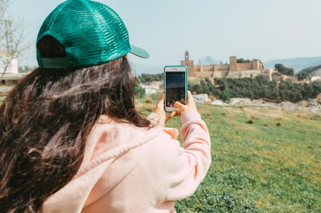 帽子をかぶった若い女性がスマートフォンで写真を撮る