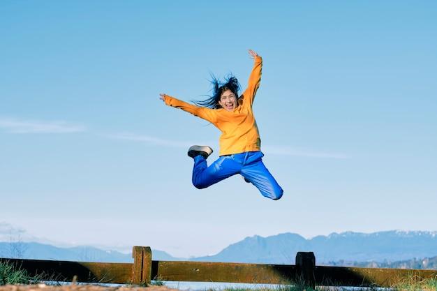 Молодая женщина в стиле хип-хоп прыгает в естественном пространстве