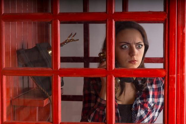 ヴィンテージの電話でおしゃべりしながら、公共の電話ブースのガラス窓から覗く恐怖の表情を持つ若い女性