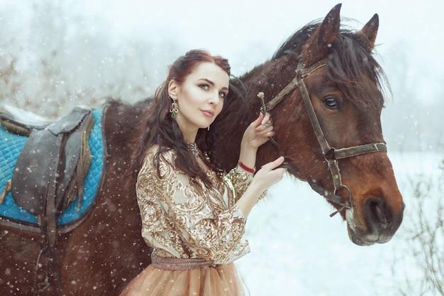 冬の公園で馬を持つ若い女