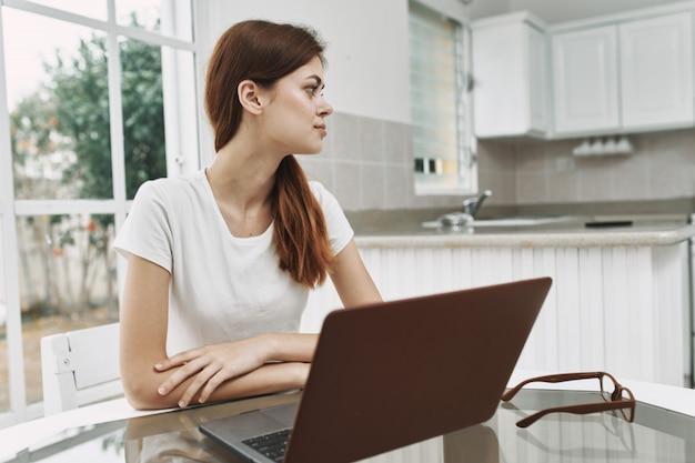 Молодая женщина с ноутбуком за столом работает и отдыхает