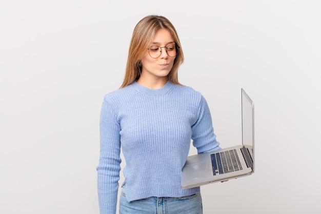 ノートパソコンを持っている若い女性は、悲しみ、動揺、または怒りを感じ、横を向いています