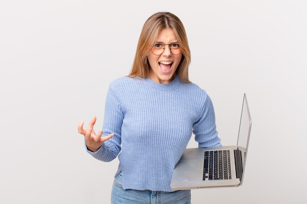 怒って、イライラして欲求不満に見えるラップトップを持つ若い女性