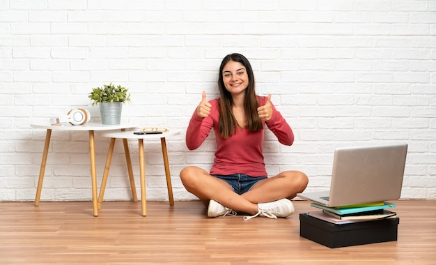 제스처를 엄지 손가락을주는 실내에서 바닥에 앉아 노트북을 가진 젊은 여자
