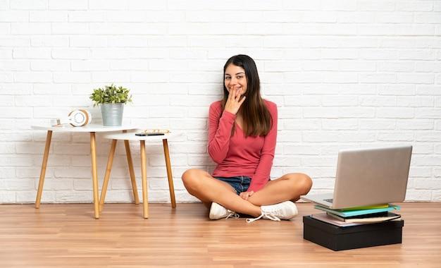 Молодая женщина с ноутбуком, сидя на полу в помещении, счастливая и улыбающаяся конусообразный рот рукой