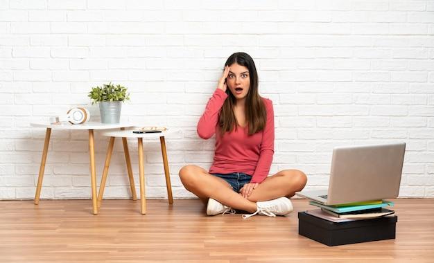 실내에서 바닥에 앉아 노트북을 가진 젊은 여자는 뭔가를 깨달았고 해결책을 의도했습니다