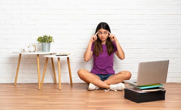 屋内で床に座っているラップトップを持つ若い女性