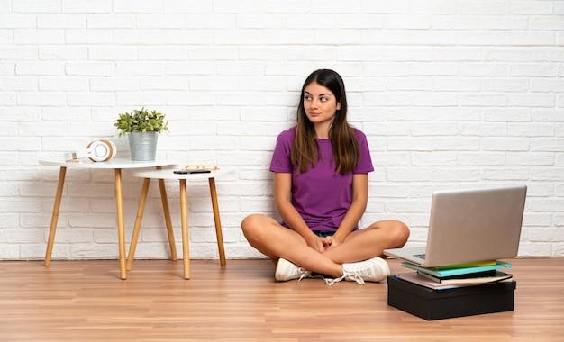 Молодая женщина с ноутбуком, сидя на полу в помещении, имея сомнения, глядя в сторону