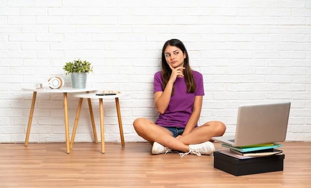 屋内で側にいると笑顔で床に座ってラップトップを持つ若い女性