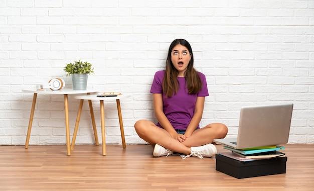 실내에서 바닥에 앉아 노트북을 찾고 놀란 표정으로 젊은 여자