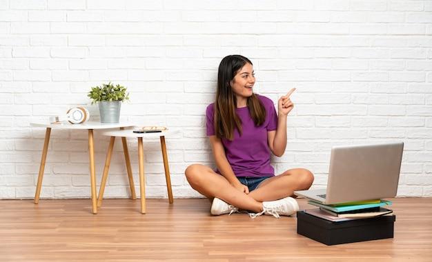 屋内の床に座って指を横に向けて製品を提示するラップトップを持つ若い女性