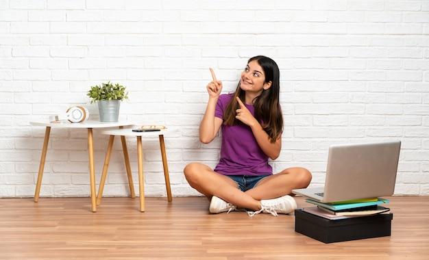 人差し指で指している屋内の床に座っているラップトップを持つ若い女性素晴らしいアイデア