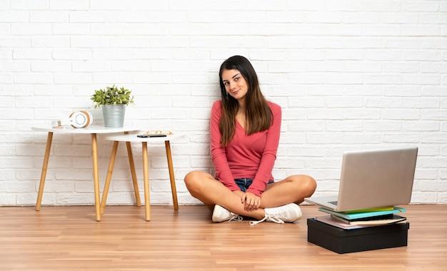 실내에서 바닥에 앉아 노트북으로 젊은 여자. 초상화