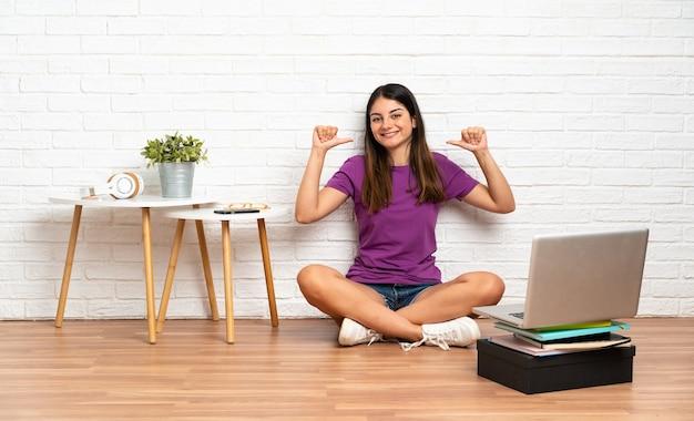 자랑스럽고 만족스러운 실내에서 바닥에 앉아 노트북을 가진 젊은 여자